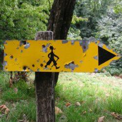 Gelbes Schild zeigt Wanderern die Richtung