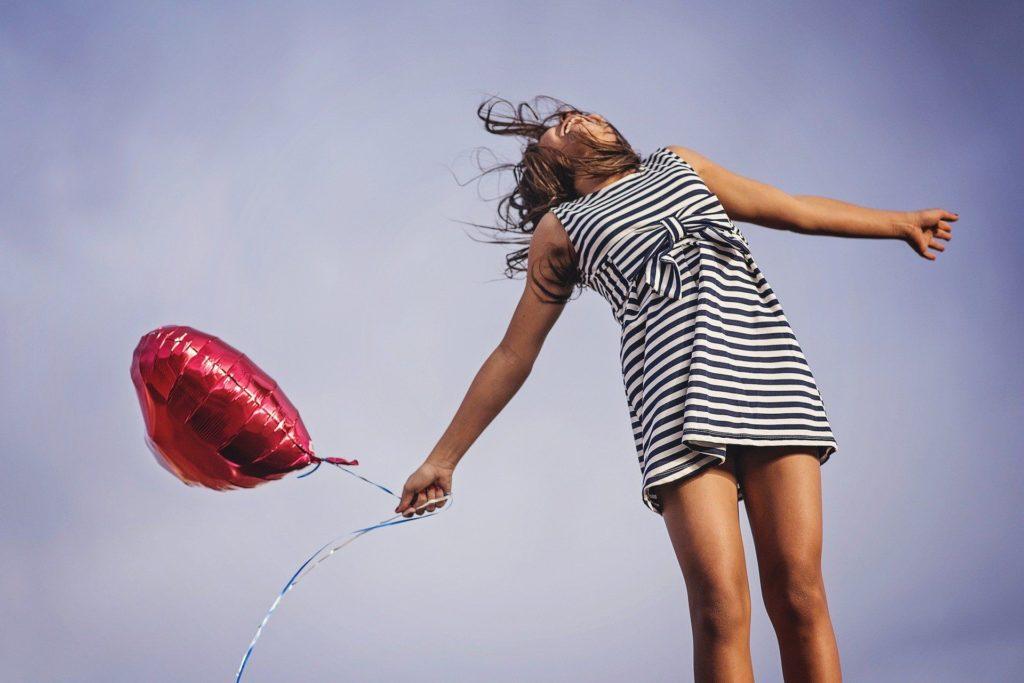 Mädchen mit Ballon springt hoch