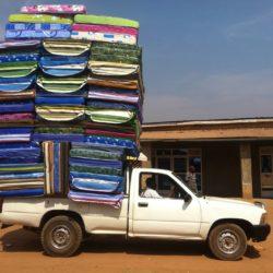 Kleiner Lieferwagen mit offener Ladefläche, auf der mehrere Dutzend Matratzen gestapelt sind